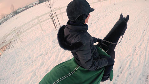 CLOSE UP: Smiling female horseback riding in winte Footage