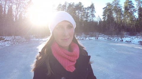 Smiling young woman ice skating on frozen lake Live Action