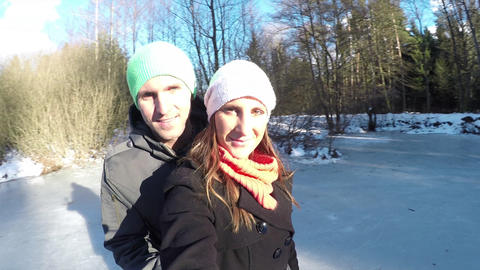 Smiling Young Couple Spinning On Ice Skates In Win stock footage
