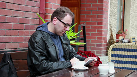 Men using tablet computer in outdoor cafe Live Action