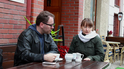 Troubled couple sitting in courtyard cafe in silen Footage