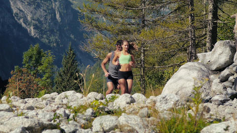 Slow Motion Of Man And Woman Running On Mountain Path Footage