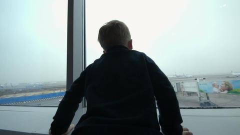 Boy looking at the plane from window and imitating Footage