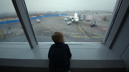 Little boy looking out the window at airport Footage