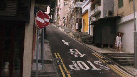 Slope road and woman moving down through footpath steps in Hong Kong, China Footage