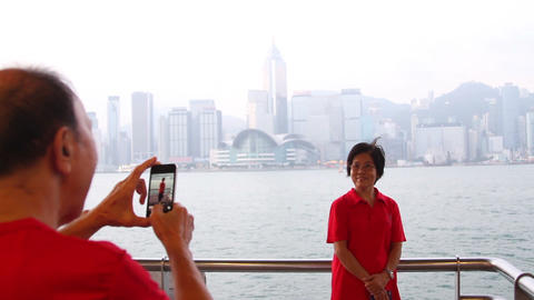 Senior man photographing with mobile phone while senior women posing for photogr Footage