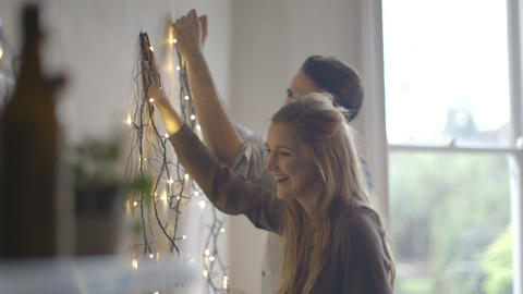 Young man and woman decorating wall with fairy lights during Christmas Live Action
