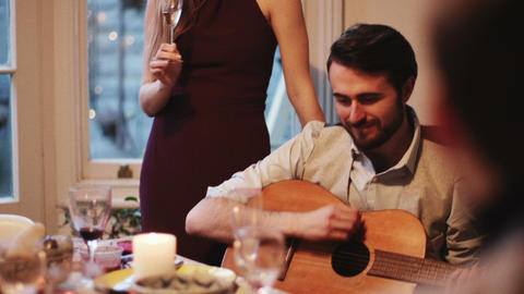 Young man playing guitar during Christmas party Live Action