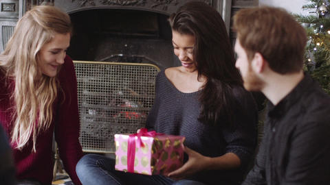 Young woman receiving gift from friends during Christmas Live Action