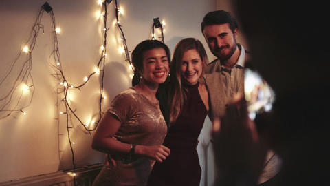 Young man and women posing for photograph at Christmas party Live Action