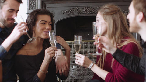 Young men and women sitting near fireplace toasting with champagne Footage
