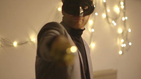 Young man in mask playing with sword during Christmas party Footage