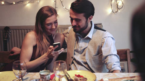 Young woman taking selfie while young man kissing her during Christmas party Live Action