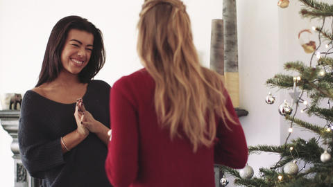 Young woman giving gift to her friend during Christmas Live Action