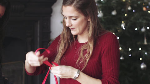 Young women wrapping Christmas gift with ribbon Live Action