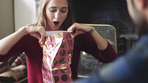 Young woman unwrapping Christmas gift Live Action