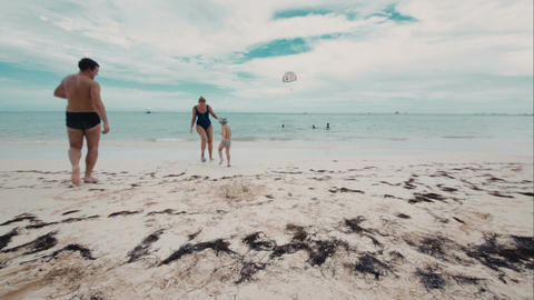 Happy family of three playing a ball on the beach Footage