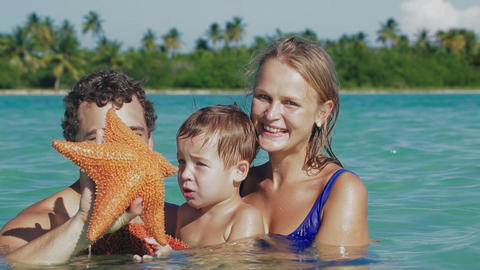 Parents and son in sea water holding starfish Live Action