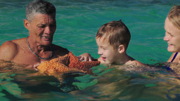 Man showing tourists two big starfish Live Action