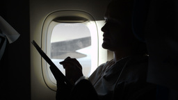 Woman sitting by illuminator in plane with touch p Footage