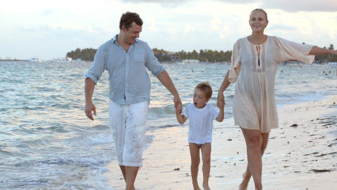 Parents and their child walking along the beach Footage