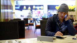 Young man in cafe making notes while talking on ph Footage