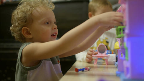 Little boys playing with toy house at home Footage