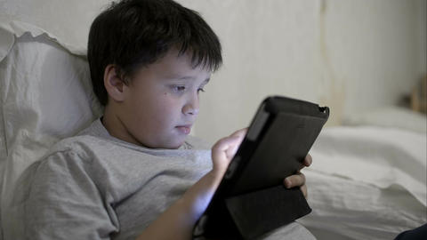 Teenager boy using tablet computer lying in bed Footage