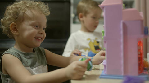Two little boys playing with toys at home Footage