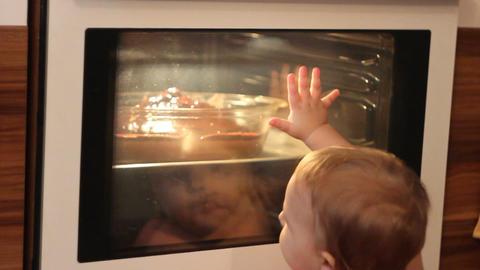 Baby looks into the oven when the cake is baked Footage