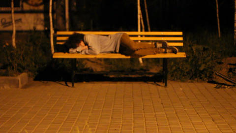 Young man lying on a bench Footage