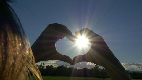 Young woman catching the sun into heart shaped han Footage