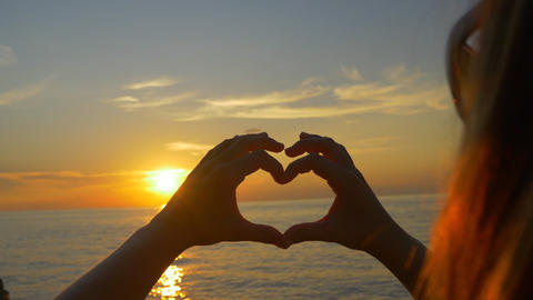 Woman looking the ocean sunset through heart hands Footage