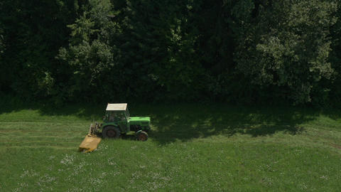 AERIAL: Tractor cutting grass in a field Footage