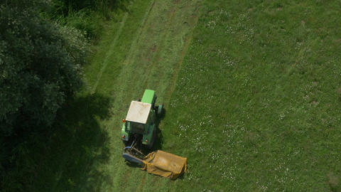 AERIAL: Flying above the tractor cutting grass Footage