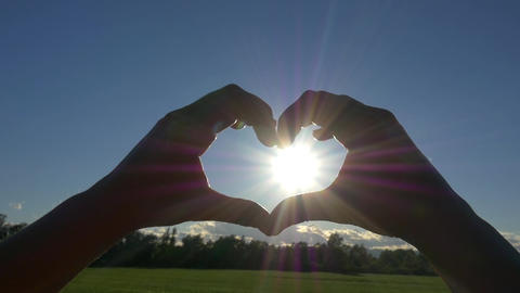 SLOW MOTION: Catching the sun into heart shaped ha Footage