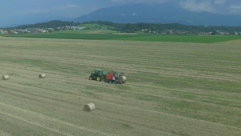 AERIAL: Tractor harvesting hay into bales on a fie Footage