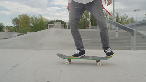 SLOW MOTION CLOSE UP: Skateboarder jumping with hi Footage