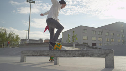 SLOW MOTION: Skateboarder does a flip over the rai Footage