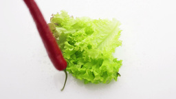 red pepper falling on lettuce slow motion Footage