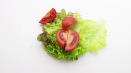 red tomato falling on lettuce slow motion Footage