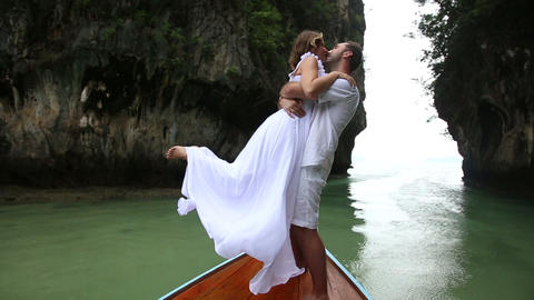 groom lifts bride by waist standing on longtail wo Footage