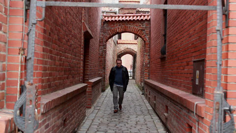 Man walking alone on narrow alley with old, Mediev Footage