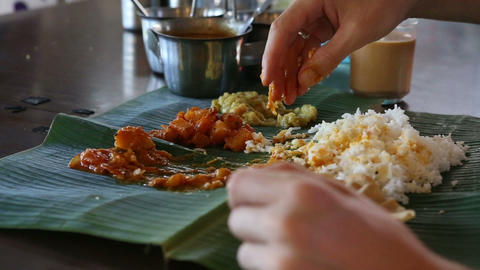 man eats food with hands from banana leaf Footage