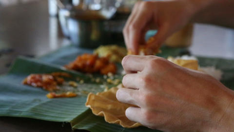 man eats rice with flat cake from banana leave Footage