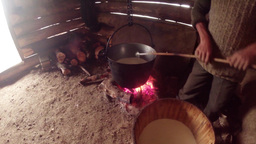 mountain shepherd mixed the milk in an iron pot in Footage