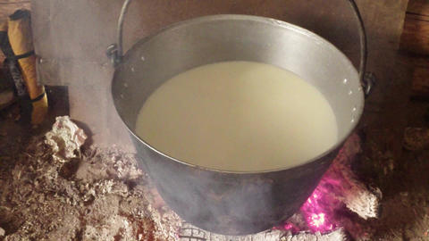 sheep milk cooked in an iron pot over a fire right Footage