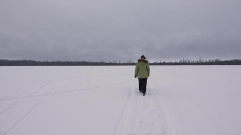 Girl walking in winter field. 4K Footage