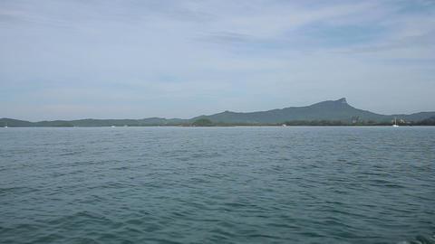 Longtail Boat Sails Along Rocky Coast stock footage