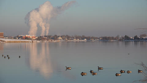 Factory Polluting Over A Lake stock footage